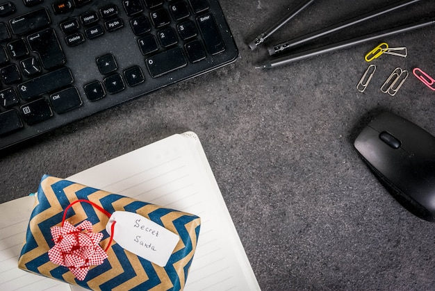 Koncepcja świątecznej uroczystości biurowej, pomysł dzielenia się prezentami w tajemnicy mikołaja. klawiatura, mysz, notatnik, długopisy, ołówki