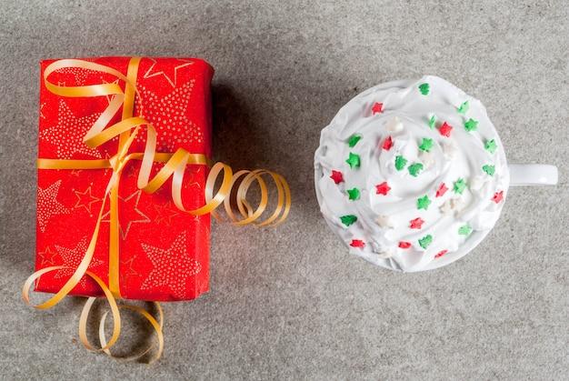 Koncepcja świąteczno-noworoczna jedno świąteczne pudełko z czerwonego papieru i kubek na kawę lub gorącą czekoladę z bitą śmietaną i dekoracją słodkich gwiazd na szarym kamiennym stole