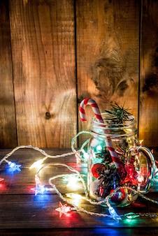Koncepcja świąteczno-noworoczna mason jar z dekoracjami świątecznymi szyszki jodły sztuczny śnieg cukierek trzcina cukrowa i gałąź jodły na drewnianym stole w tle z włączoną oświetloną girlandą