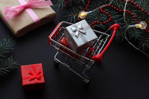 Koncepcja świątecznych zakupów wózek spożywczy z prezentami na świątecznym tle wyprzedaże na święta zimowe