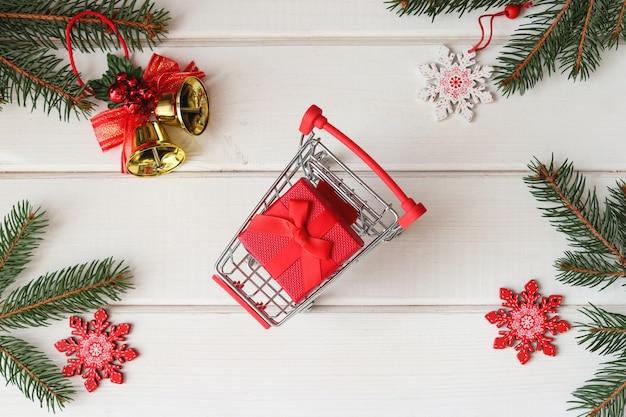 Koncepcja świątecznych zakupów wózek spożywczy z prezentem na świątecznym drewnianym tle ferie zimowe