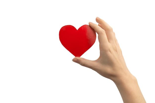Koncepcja światowego dnia serca. ręka trzyma czerwone serce na białym tle na białym tle. skopiuj zdjęcie miejsca