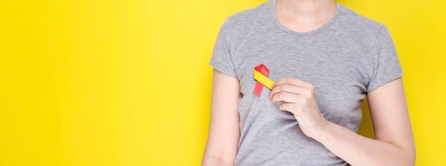 Koncepcja światowego dnia zapalenia wątroby. dziewczyna w szarej koszulce trzyma w ręku symbol świadomości czerwono-żółtą wstążkę