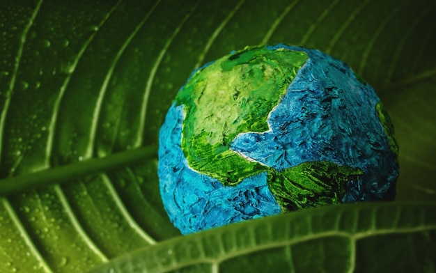 Koncepcja światowego dnia ziemi. zielony liść wilgoci z kroplami wody obejmujący ręcznie robioną kulę. środowisko do miłości i troski
