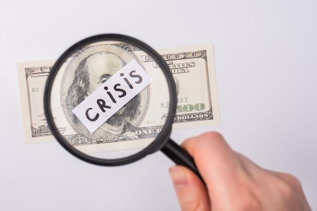 Koncepcja światowej recesji 2020. przycięte zdjęcie kobiecej dłoni za pomocą lupy patrząc na 100 amerykańskich banknotów na białym tle nad szarym tłem
