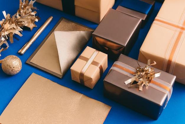 Koncepcja święta bożego narodzenia ze złotymi pudełkami, kopertą, wieńcem