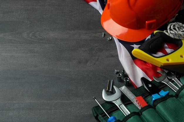 Koncepcja święto pracy z różnymi narzędziami budowlanymi na ciemnym drewnianym