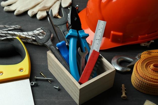 Koncepcja święto pracy z różnymi narzędziami budowlanymi na ciemnym tle drewnianych