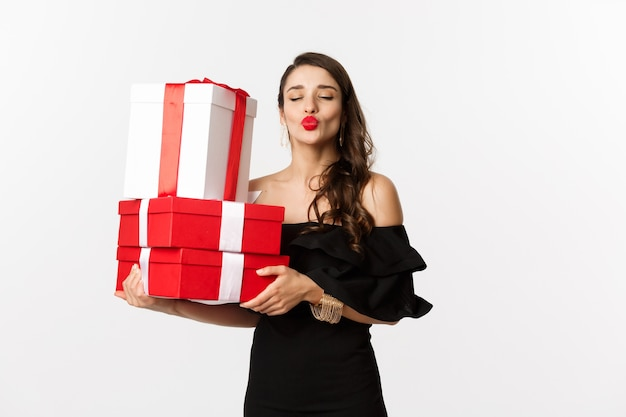 Koncepcja świętowania i świąt bożego narodzenia. głupia kobieta w eleganckiej czarnej sukni, trzymając prezenty świąteczne i noworoczne, zmarszczone usta do pocałunku, stojąca szczęśliwa na białym tle.