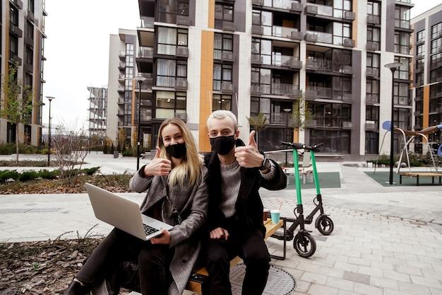 Koncepcja świeżego powietrza. młoda kobieta trzyma nowoczesny laptop i patrząc na kamery, mężczyzna w ubranie kciuk w górę i siedzi na ławce. para zachowuje dystans od innych ludzi.