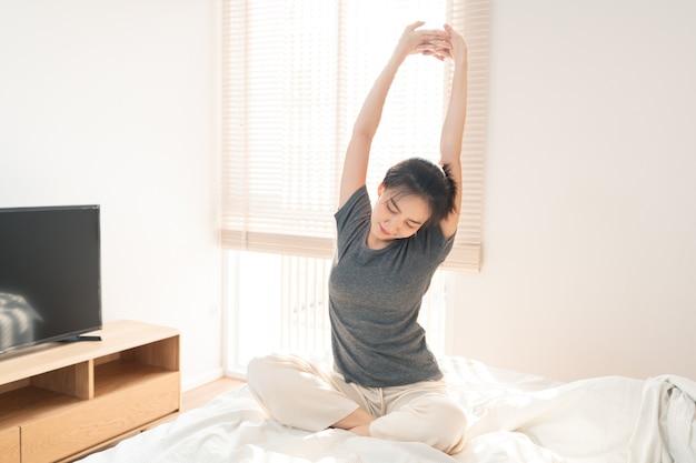 Koncepcja sypialni ładna dziewczyna wygląda na senną ziewanie, wyciągając rękę na białym wygodnym łóżku.