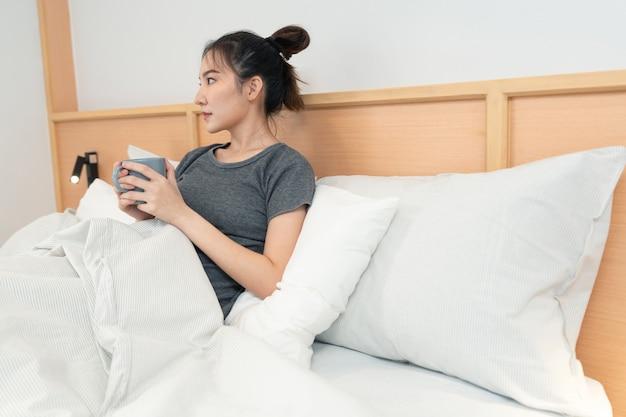 Koncepcja sypialni w łóżku dziewczyna doceniająca zapach i smak gorącej kawy w dłoniach patrząca za okno.