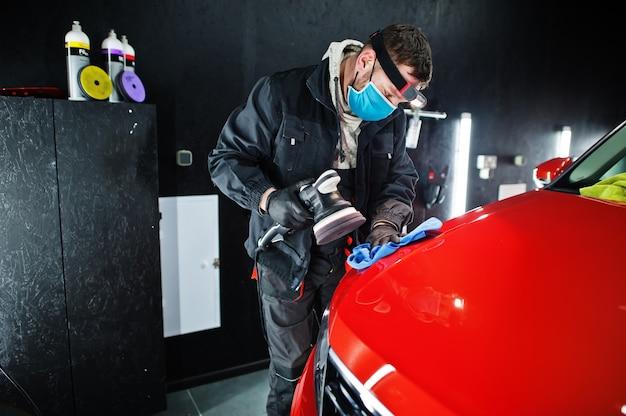 Koncepcja szczegółowości samochodu. mężczyzna w masce z polerką orbitalną w warsztacie polerującym pomarańczowy samochód suv.
