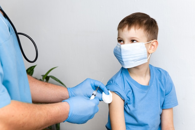 Koncepcja szczepień. mężczyzna lekarz szczepi ładny mały chłopiec w klinice, zbliżenie. sesja szczepień przeciwko koronawirusowi covid-19 i poprawie odporności
