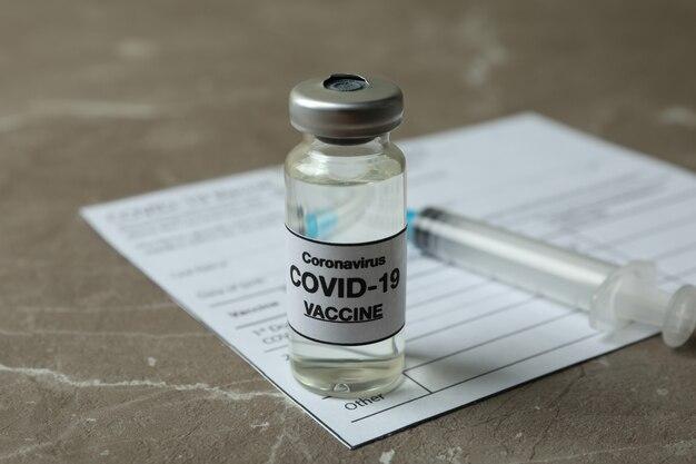 Koncepcja szczepienia covid - 19 szczepionką i strzykawką na szarym stole z teksturą