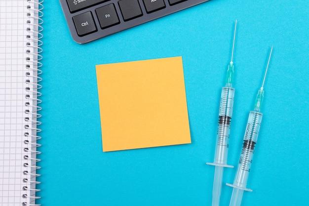 Koncepcja szczepienia lub ponownego szczepienia dwie strzykawki medyczne na niebieskim stole