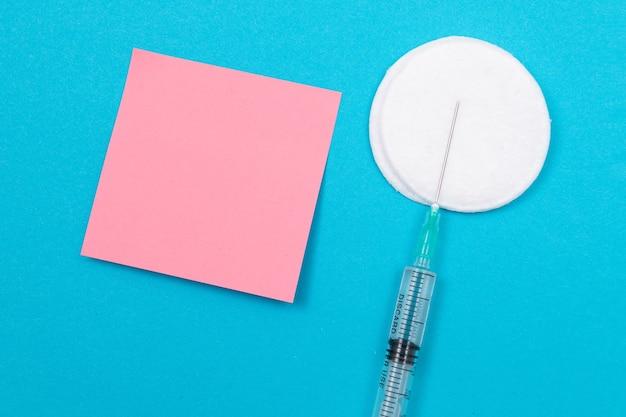 Koncepcja szczepienia lub ponownego szczepienia medyczna strzykawka na niebieskim stole