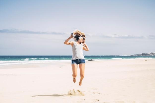 Koncepcja szczęścia i radosnych ludzi z młodą piękną kędzierzawą kobietą rasy kaukaskiej skaczącym jak szalony na plaży podczas letnich wakacji rekreacyjnych - słuchawki i telefon komórkowy