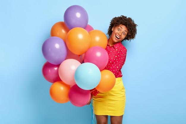 Koncepcja szczęścia i świętowania. uradowana ciemnoskóra kobieta wita przyjaciół z wyjątkowej okazji