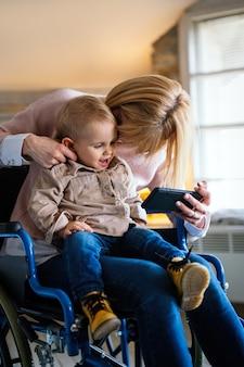 Koncepcja szczęścia rodzinnego technologii osób. szczęśliwa matka niepełnosprawna na wózku inwalidzkim z dzieckiem korzystająca z cyfrowego tabletu w domu