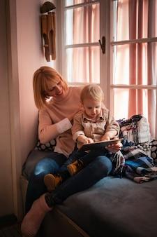 Koncepcja szczęścia rodzinnego technologii osób. szczęśliwa matka z dzieckiem korzystająca z cyfrowego tabletu w domu