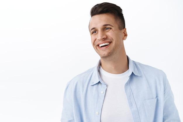 Koncepcja szczęścia, rodziny i emocji. szczegół portret przystojnego szczęśliwego młodego mężczyzny ze stylową fryzurą, odwróć wzrok pozostawioną pustą przestrzeń z zadowolonym wesołym uśmiechem, śmiejąc się i ciesząc