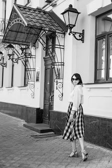 Koncepcja szczęścia - szczęśliwa kobieta, zabawy na ulicy miasta. kobieta moda w okularach przeciwsłonecznych idzie ulicą na wysokich obcasach. obraz czarno-biały