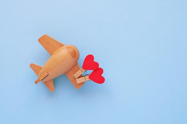 Koncepcja szczęśliwy walentynki. eko drewniany samolot dla dzieci na niebieskim tle z czerwonym sercem.