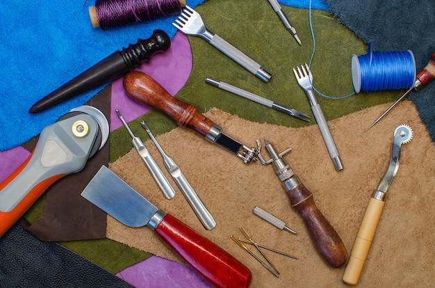 Koncepcja szewca skóry. skórzany biznes, narzędzie jest rozłożone na kawałkach kolorowej skóry.