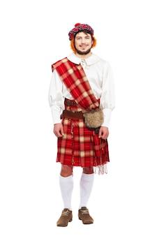 Koncepcja szkockich tradycji z osobą noszącą kilt na białym tle