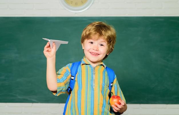 Koncepcja szkoły dziecko w szkole podstawowej przy biurku dziecko z edukacją papierowego samolotu i małą nauką