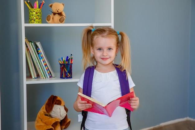 Koncepcja szkoły edukacji. mała dziewczynka z książką w ręku