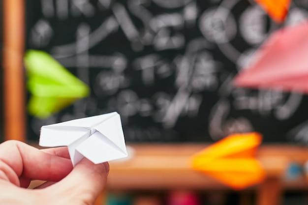 Koncepcja szkoły, ręka uruchamia mały papierowy samolot na tablicy szkolnej, uniwersytecie, college'u