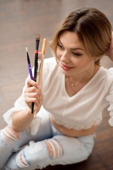 Koncepcja sztuki, kreatywności, pracy i kreatywnego zawodu. artystka pozuje przed oknem i maluje farbą olejną lub akrylową