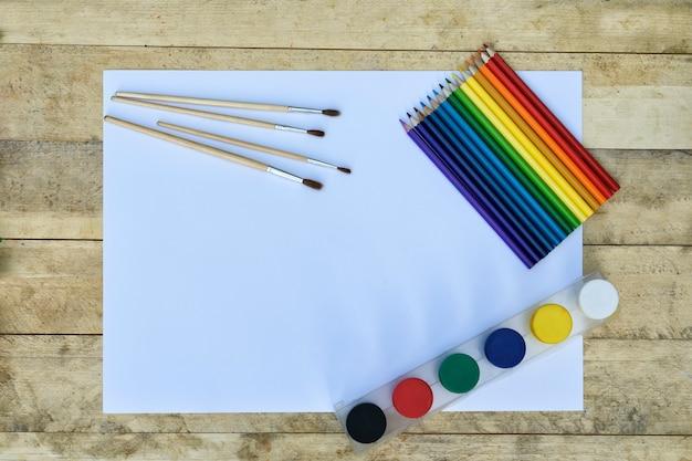 Koncepcja sztuki. pusty arkusz papieru, farby, pędzle i kredki.