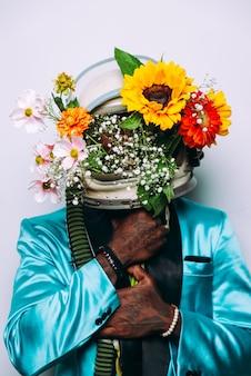 Koncepcja sztuki z mężczyzną w hełmie kosmicznym i kompozycją kwiatów