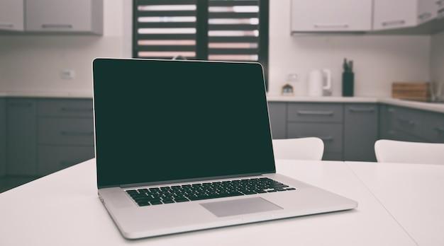 Koncepcja szukania receptur z nowoczesnym laptopem na stole w kuchni