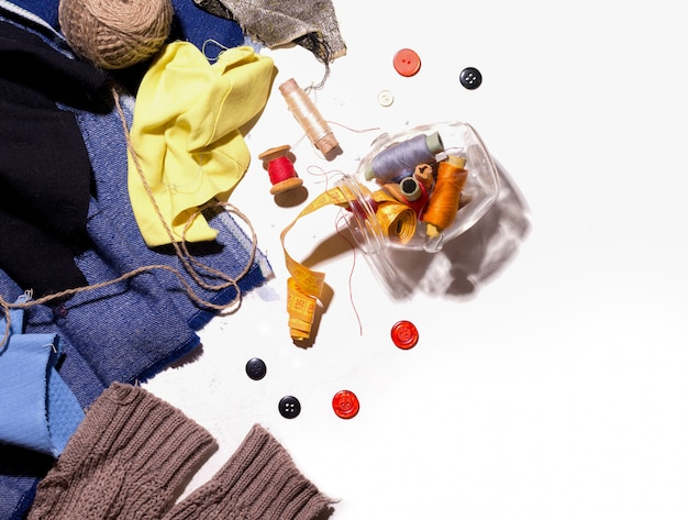 Koncepcja szycia ze starych rzeczy i kawałków tkaniny. na białej nici guziki. skopiuj miejsce