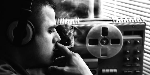 Koncepcja tajnych służb fbi. agent specjalny podsłuchuje na magnetofonie szpulowym. oficer podsłuchuje w słuchawkach. szpiegowanie rozmów przez kgb.