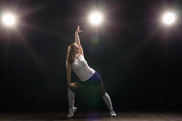 Koncepcja tańca, hip-hopu, jazzu funk i ludzi - elastyczna młoda kobieta tańczy w ciemności pod światłem.