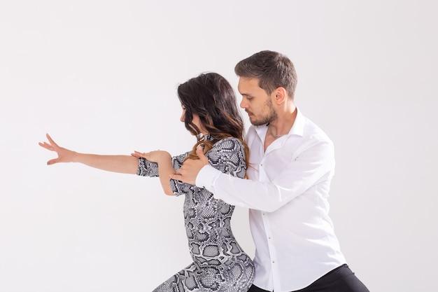 Koncepcja tańca społecznego - aktywni szczęśliwi dorośli razem tańczący bachata lub salsa na białym tle