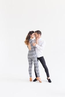 Koncepcja tańca społecznego - aktywni szczęśliwi dorośli razem tańczący bachata na białym tle