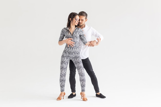 Koncepcja tańca społecznego - aktywni szczęśliwi dorośli tańczą razem bachatę na białym tle z miejscem na kopię
