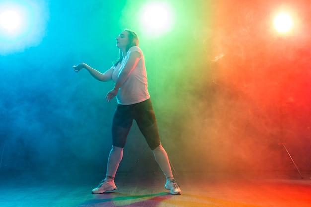 Koncepcja tańca, sportu i ludzi - młoda kobieta tańczy w ciemności pod kolorowym światłem.
