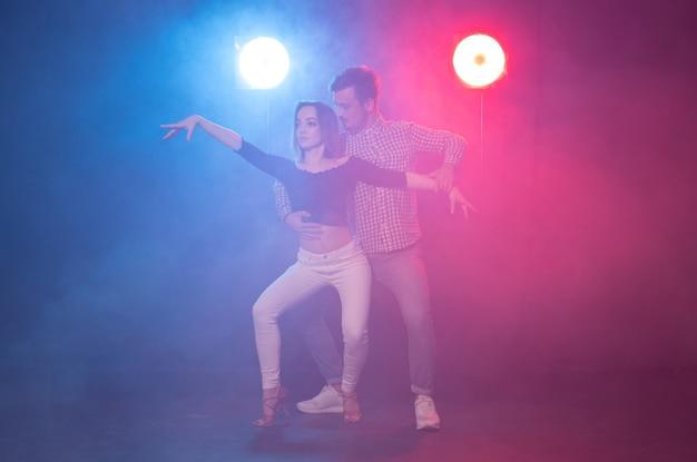 Koncepcja tańca towarzyskiego, kizomby, salsy, semby lub zouk - młoda para tańcząca bachatę i salsę na dyskotece