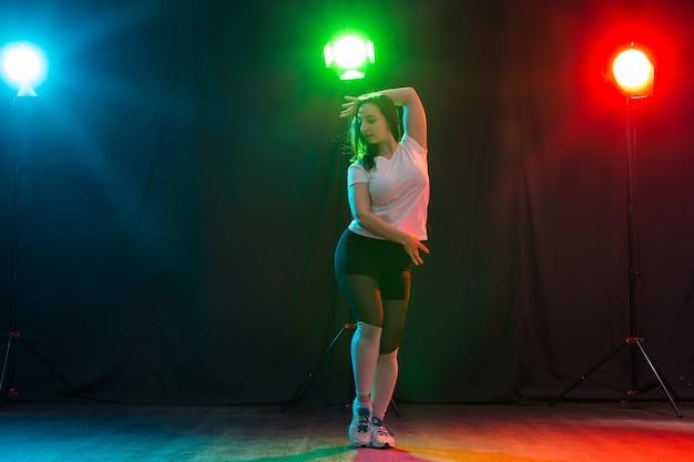 Koncepcja tańca współczesnego, sportu i ludzi - młoda kobieta tańczy jazz funk w ciemności pod kolorowym światłem.