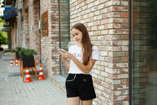 Koncepcja technologii, emocji, ludzi, muzyki, urody, mody i stylu życia - młoda kobieta ze słuchawkami zwisającymi na telefonie komórkowym, gdy idzie ulicą miejską, widok z wysokości