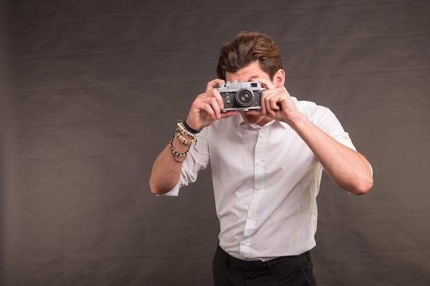 Koncepcja technologii, fotografii i hobby - człowiek z aparatem w stylu retro, robiący ci zdjęcie na szarej powierzchni z miejscem na kopię