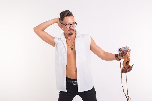 Koncepcja technologii, fotografii i ludzi - młody przystojny mężczyzna w koszuli, biorąc selfie nad białym