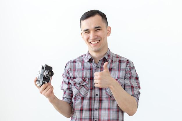 Koncepcja technologii, fotografowania i ludzi - przystojny azjatycki młody człowiek z aparatem retro